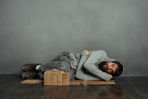 Beggar man lying on the floor homeless depression help money problems