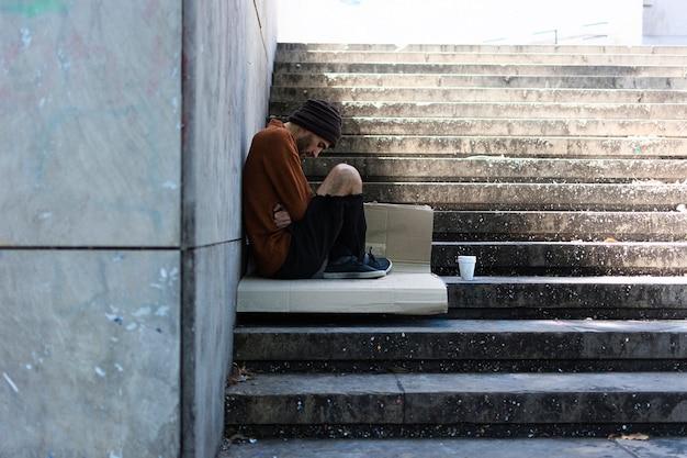 Нищий человек ждет на улицах города