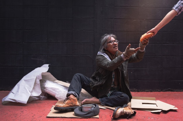 The beggar's hand reaches for bread from a donation