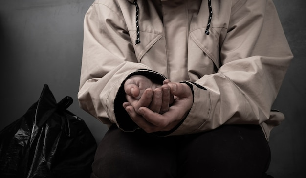 A beggar with outstretched hands asks for money sits on the floor.