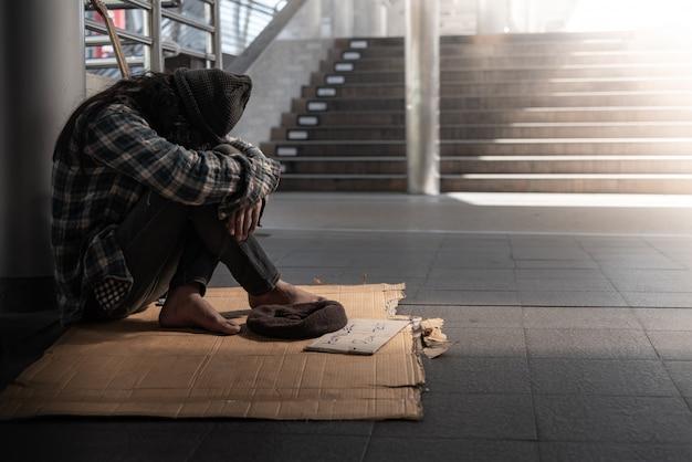 거지, 노숙자가 바닥에 앉아 금지령에 가까워지고 돈을 조금 요구합니다
