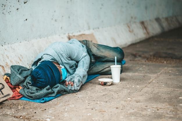 汚い服を着て通りの端に横たわる乞食。