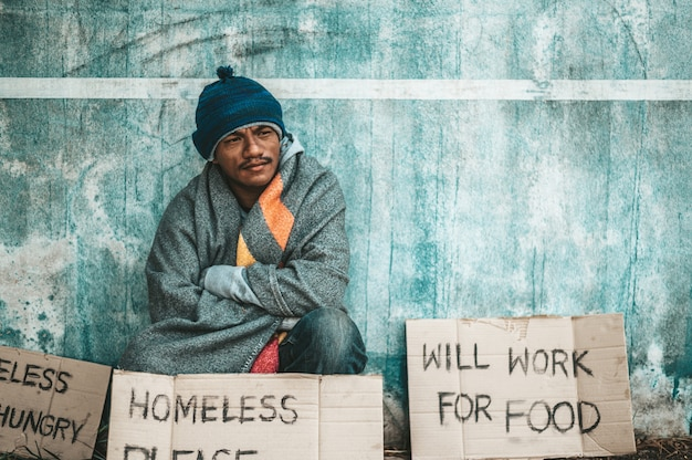 The beggars sat beside the street with a homeless message. please help and work with food.