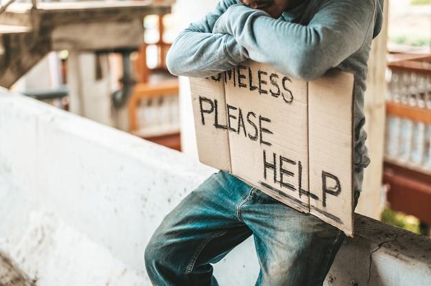 乞食はホームレスで障壁に座りますメッセージを助けてください。