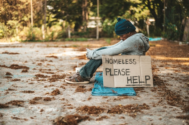 ホームレスのメッセージで通りに座っている乞食が助けてください。