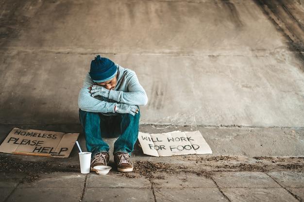 カップのある橋の下に座っている乞食はお金を持っています。