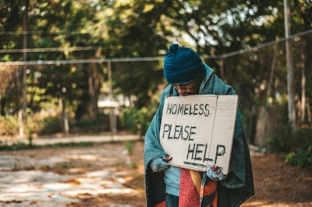 Beggars stand on the street with homeless messages please help.