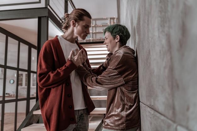 懇願する彼氏。攻撃的な感情的なボーイフレンドに彼女を殴らないように懇願する緑髪のガールフレンド
