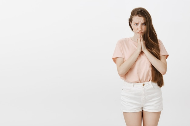 Accattonaggio carino ragazza adolescente in posa contro il muro bianco