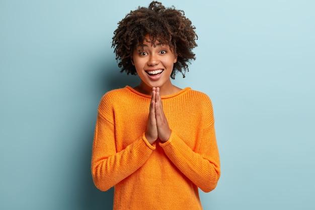 Mendicare felice femmina dalla pelle scura tiene le mani in gesto di preghiera, ha uno sguardo implorante, un'espressione positiva, chiede supporto e aiuto, indossa un maglione casual arancione, modelli sul muro blu