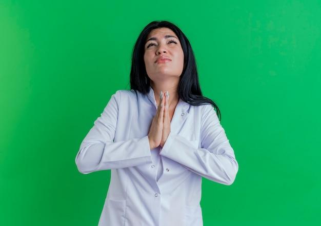 祈りのジェスチャーで手を一緒に保ちながら見上げる医療ローブを着て若い女性医師を懇願する