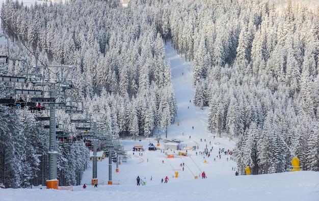 Лыжная трасса для начинающих и открытый кресельный подъемник в солнечный зимний день