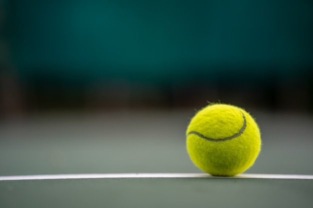 The beginning of a champion, close up tennis ball on the courts background.