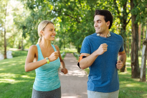 Beginning of the day. joyful positive couple smiling to each other while jogging in the morning together