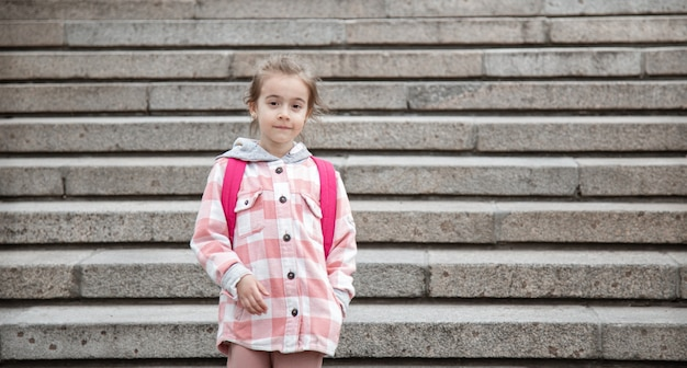 The beginning of lessons and the first day of autumn. a sweet girl stands against large wide staircase.