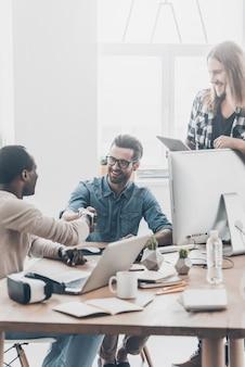 Начало нового партнерства. группа молодых деловых людей, работающих вместе в офисе, в то время как двое мужчин пожимают друг другу руки и улыбаются