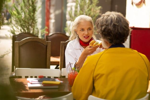 하루의 시작. 성인 남편과 아내가 거리 카페에 앉아 식사를 하고 신시가지를 산책합니다.