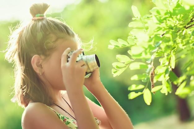 Начинающий фотограф. маленькая девочка фотографирует дерево на своем пленочном фотоаппарате