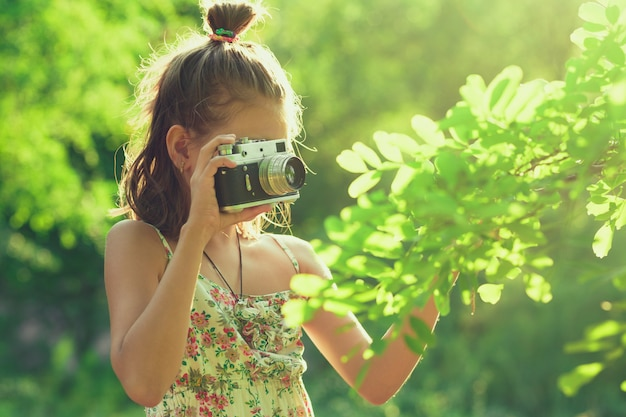 Beginning photographer. a little girl takes pictures of a tree on her film photo camera