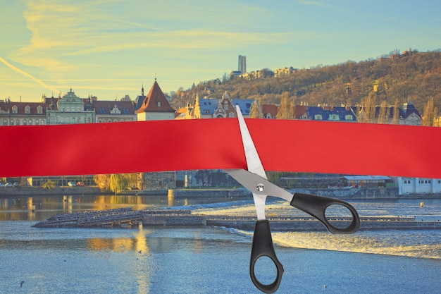 The beginning of the tourist season, the end of quarantine, the opening of the borders of countries. scissors cut a red ribbon with a view of prague, czech republic