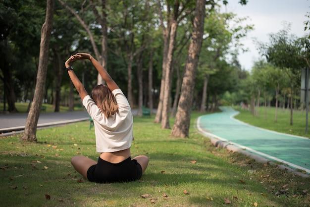 庭で運動した後、ストレッチ草の上に座っている若いアジアの女性の後ろ