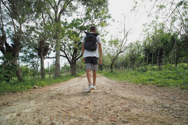 검은 배낭을 든 남자의 뒤에서 시골 길을 걷는다.
