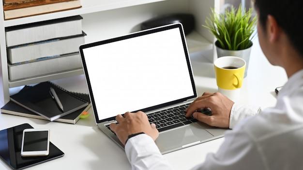 オフィス機器に囲まれたモダンな作業テーブルに座って、白い空白の画面でコンピューターラップトップに入力するデータアナリストとして働いている若いスマートな男の後ろ。