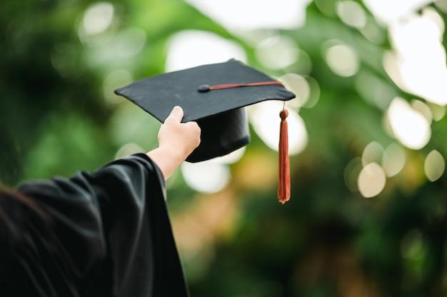 대학 졸업자의 사진 뒤에는 가운과 검은색 모자 갈색 술이 있습니다.