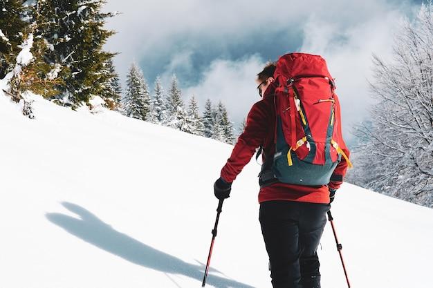 눈 덮인 산에서 남자 스키 등산의 총 뒤에