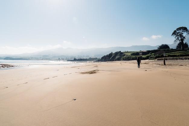 Позади снимка женщины, идущей по пляжному песку у берега с горами