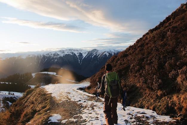 雪に覆われた山のハイカーの後ろのショット