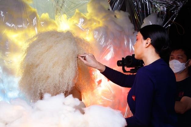 20대 아시아 아름다운 여성 금발의 아프로 헤어 하이 패션 메이크업의 하프 바디 초상화의 메이크업 아티스트의 무대 뒤에서. 귀여운 소녀 미소는 스튜디오에서 파스텔 색상의 구름 위에 카메라를 보고 있습니다.
