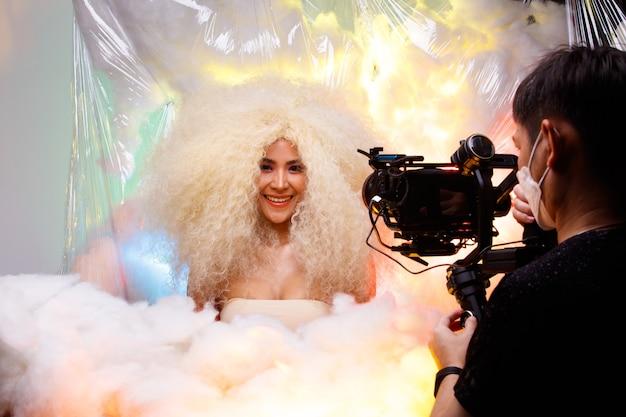 20대 아시아 아름다운 여성 금발의 아프리카 머리 하이 패션의 하프 바디 초상화의 비디오 그래퍼의 무대 뒤에서. 귀여운 소녀 미소는 스튜디오에서 파스텔 색상의 구름 위에 카메라를 보고 있습니다.