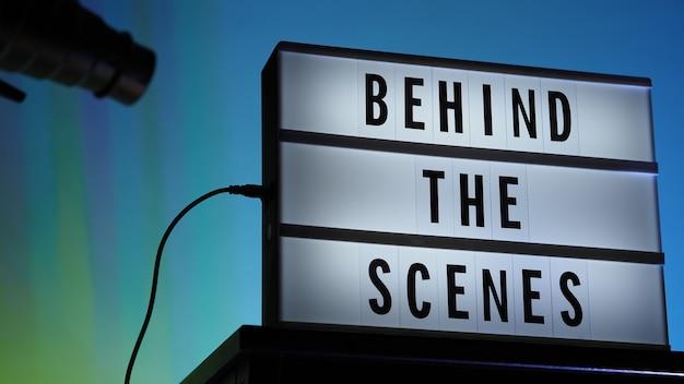ライトボックスまたはシネマライトボックスの舞台裏のレターボードテキスト。マルチカラーled。三脚のシルエットフラッシュスヌートフード。ビデオ制作スタジオ。舞台裏ライトボックス