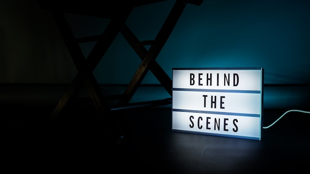 舞台裏のライトボックス。シネマライトボックスのテキスト。メガホンとディレクターズチェアと映画のスレートが横にあります。舞台裏のコンセプト。