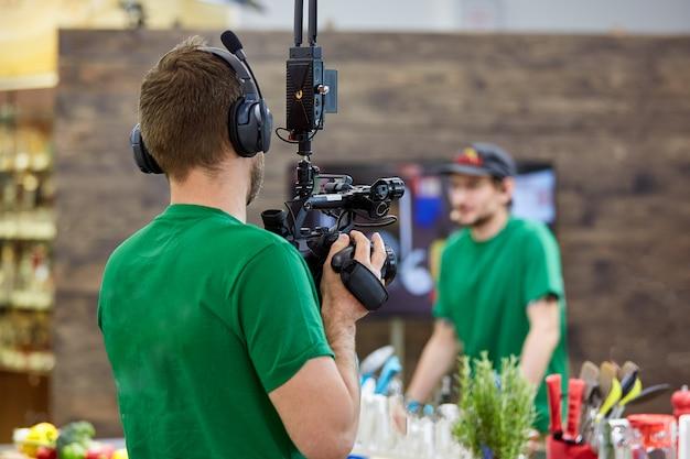 映画撮影やビデオ制作の舞台裏で、屋外の場所にカメラ機器を備えたフィルムクルーのチーム。