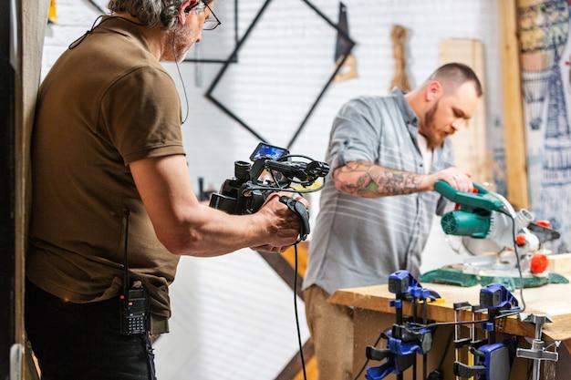 За кулисами производства для операторской съемки видеоаппаратуры, установленной сцены с работником