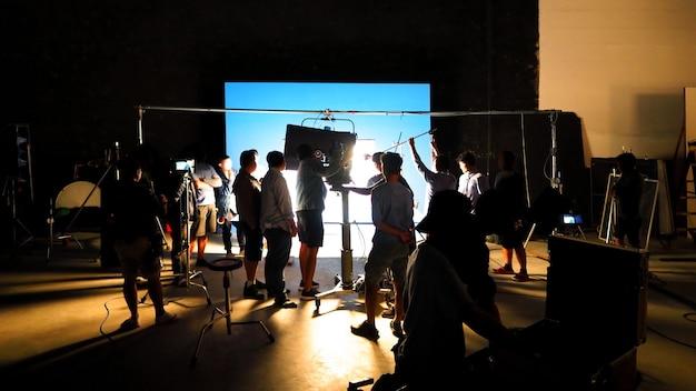 За кулисами видеопродукции, съемочная студия в силуэте, у которой есть профессиональные
