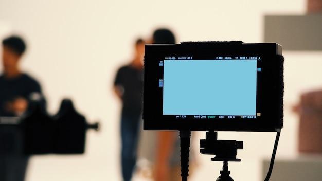 За видеопроизводством цифровой экран монитора с кинокамерой в студии.