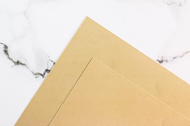 Бежевая бумага на белом мраморном фоне в виде офисных канцелярских принадлежностей, роскошный брендинг, плоский дизайн и фирменный стиль для макетов