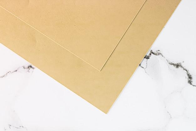 Бежевые бумаги на белом мраморном фоне в виде офисных канцелярских принадлежностей, роскошных брендов, плоских и ...