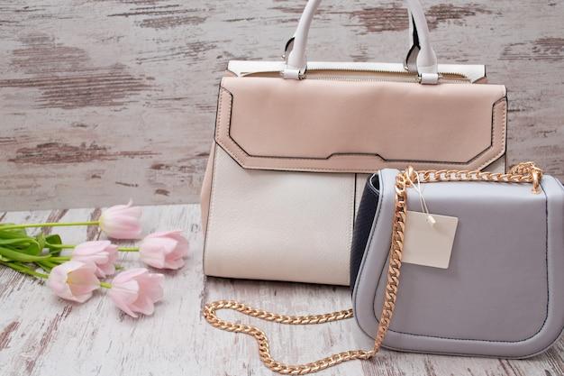 Бежевые и серые сумки на деревянном фоне, розовые тюльпаны. модная концепция.