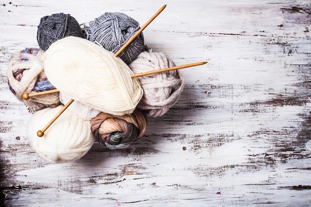 ベージュとグレーの色の糸とコピースペース付きの木製の編み針