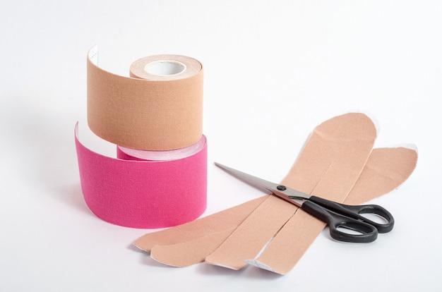スポーツ中や白い表面にハサミで怪我をした後の筋肉を固定するためのベージュとピンクのテープ。アスリートの運動学的テーピング。リハビリと回復。