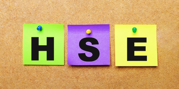 On a beige background, multicolored stickers for notes with the word hse.