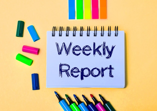 On a beige background, a notebook with the words weekly report, bright felt-tip pens and stickers
