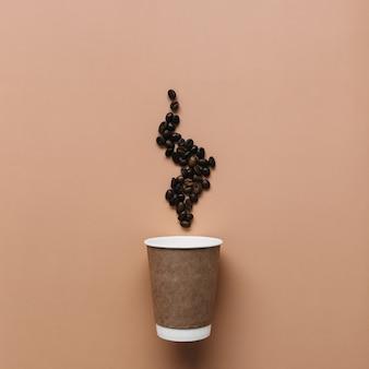 Бежевый фон с бумажной кофейной чашкой, паром кофейных зерен от горячего кофе.