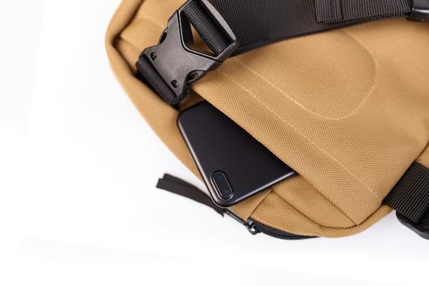 携帯電話のための隠されたポケットと白い背景と分離ベージュバッグをクローズアップ