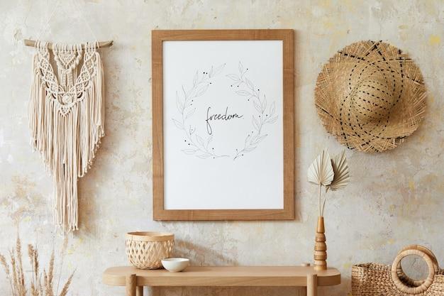 포스터 프레임, 우아한 액세서리, 꽃병에 말린 꽃, 나무 콘솔 및 세련된 가정 장식에 매달려있는 마크라메가있는 거실의 베이지 색 boho 인테리어.