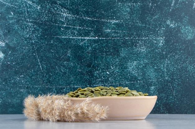 돌에 껍질을 벗긴 호박 씨앗의 베이지색 그릇입니다.
